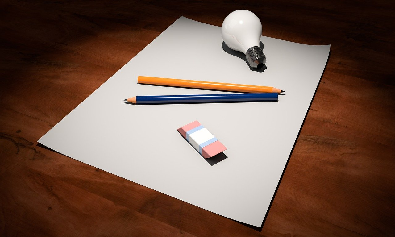 A sheet of paper with pencils, rubber and light bulb sitting on it.